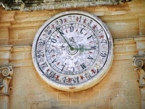 A clock showing days and months on a church in the Mdina